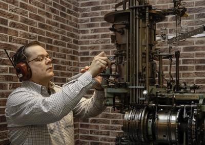 Konemestari Jukka Pesonen tekemässä päivittäistä ylläpitohuoltoa, jonka ansiosta vuosikymmeniä vanhat koneet palvelevat edelleen moitteettomasti.